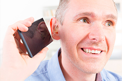 A man trying to hear on the phone