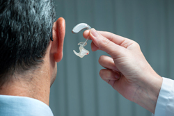Doctor Fitting Patient With Hearing Aid