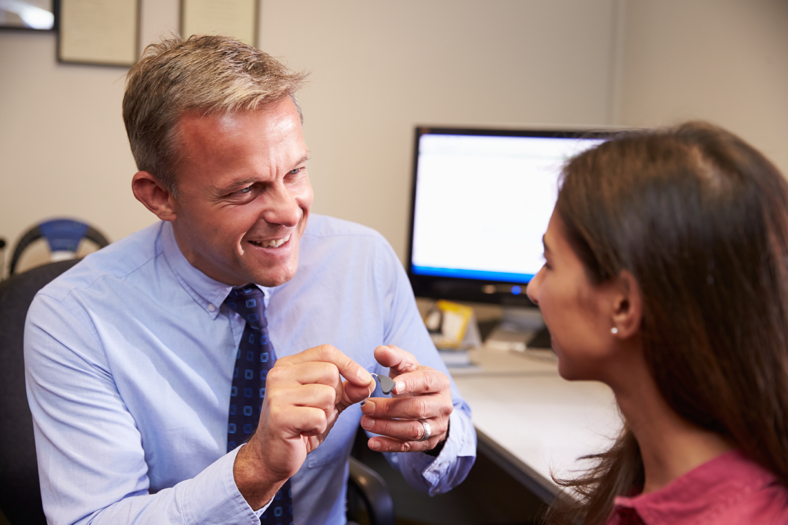 Audiologist Fitting Female Patient With Hearing Aid