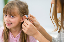 A female hearing specialist putting a hearing aid device on a little girl