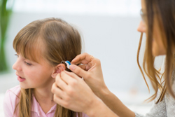 Hearing Aid Specialist Fitting Hearing Aid On Child