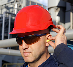 Construction Worker Protecting Ears with Plugs