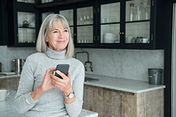 Senior Woman Adjusting Hearing Aids With Smartphone
