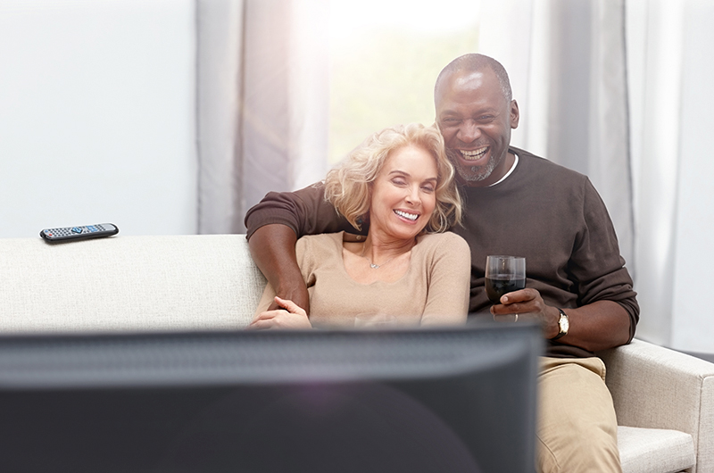 Loving Couple Enjoying Watching TV With Wireless Hearing Aids