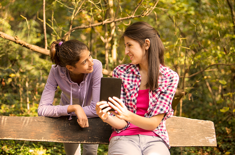 Teen Girls Listening To Tablet Using Wireless Hearing Aids