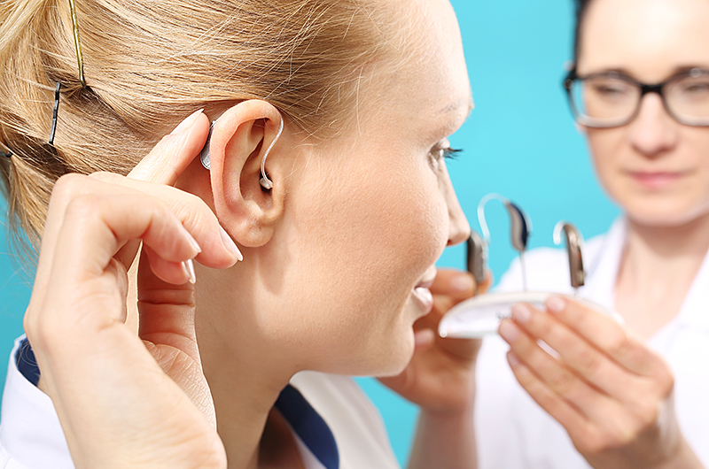 Woman Trying On Wireless Hearing Aid